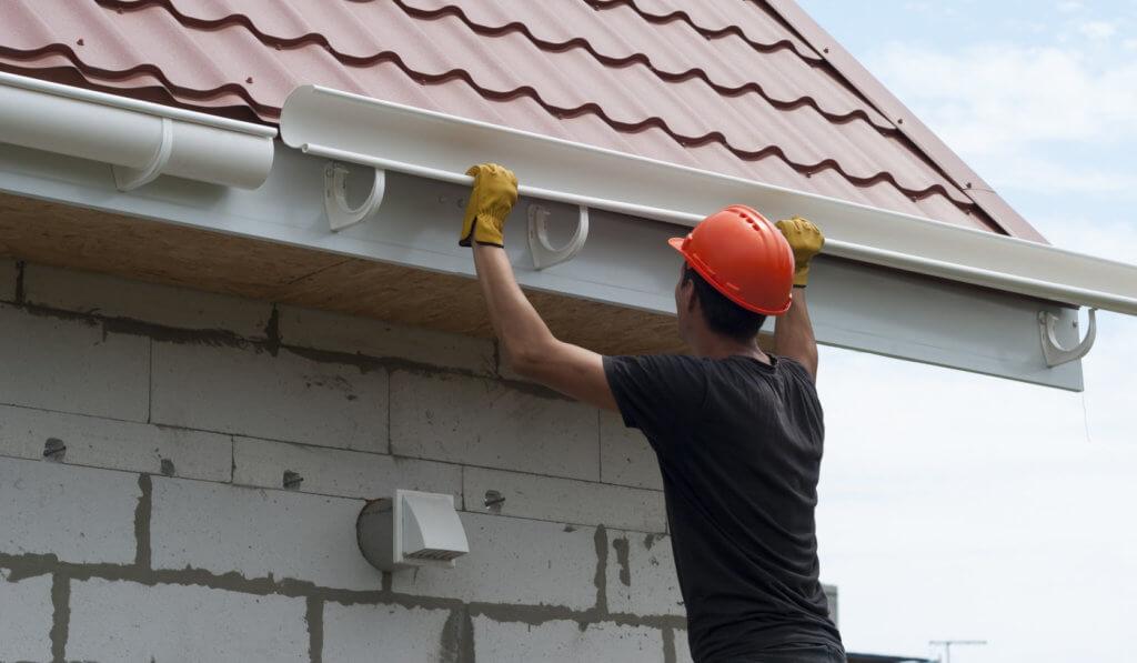 man installing gutters