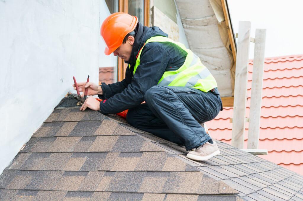 man making roof repairs