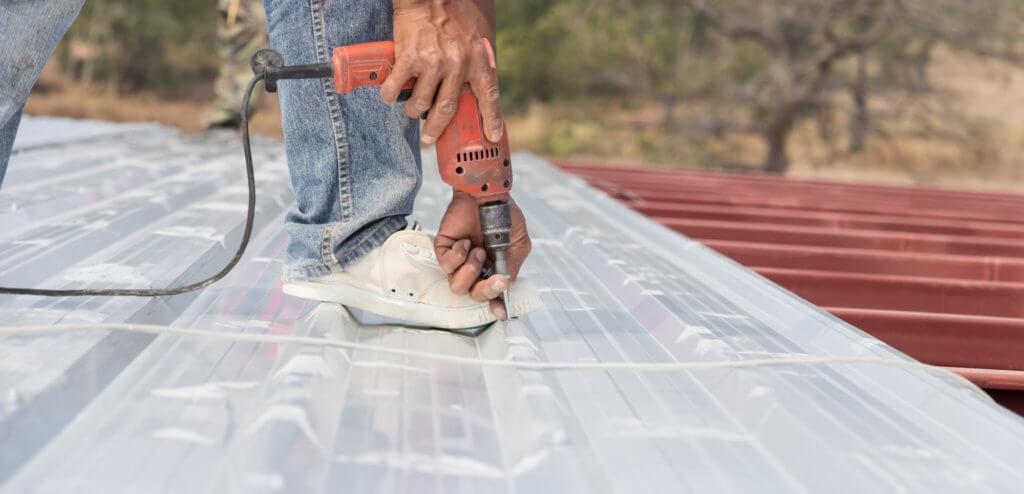 man working on metal roof